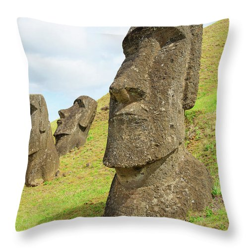 Tranquility Throw Pillow featuring the photograph Three Moai Half Buried In A Quarry by Volanthevist
