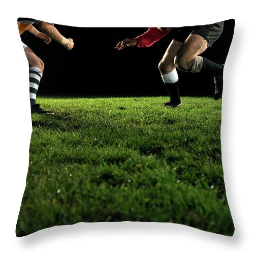 Grass Throw Pillow featuring the photograph Two Opposing Rugby Players, One Holding by Thomas Barwick