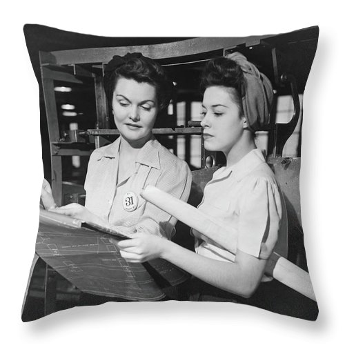Plan Throw Pillow featuring the photograph Two Women In Workshop Looking At by George Marks