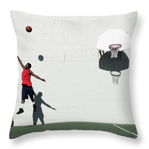 Young Men Throw Pillow featuring the photograph Two Young Men Playing Basketball by Thomas Barwick