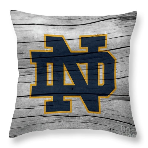 Football Throw Pillow featuring the photograph University Of Notre Dame Fighting Irish Logo On Rustic Wood by John Stephens