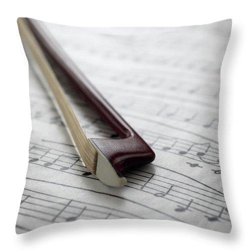 Sheet Music Throw Pillow featuring the photograph Violin Bow On Music Sheet by Daniel Allan