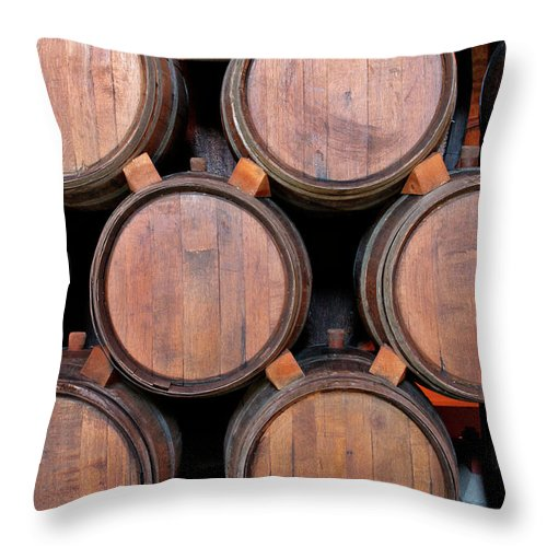 Fermenting Throw Pillow featuring the photograph Wine Barrels Stacked Inside Winery by Yinyang