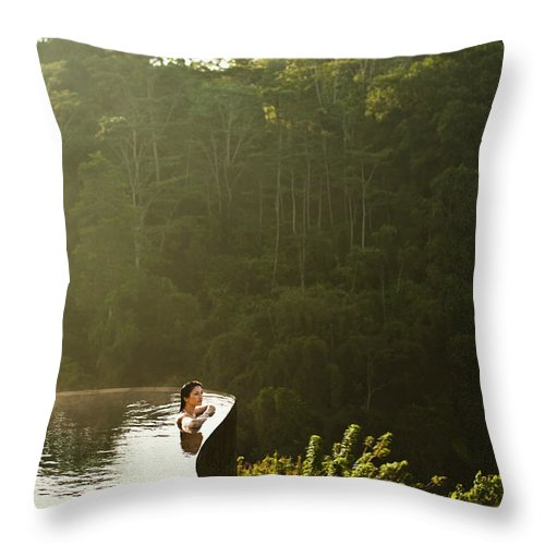 Tropical Rainforest Throw Pillow featuring the photograph Woman In Infinity Pool At Sunrise. Bali by Matthew Wakem