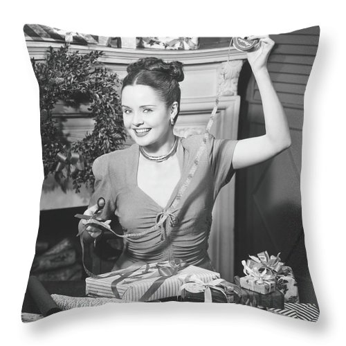 Human Arm Throw Pillow featuring the photograph Woman Wrapping Christmas Presents In by George Marks