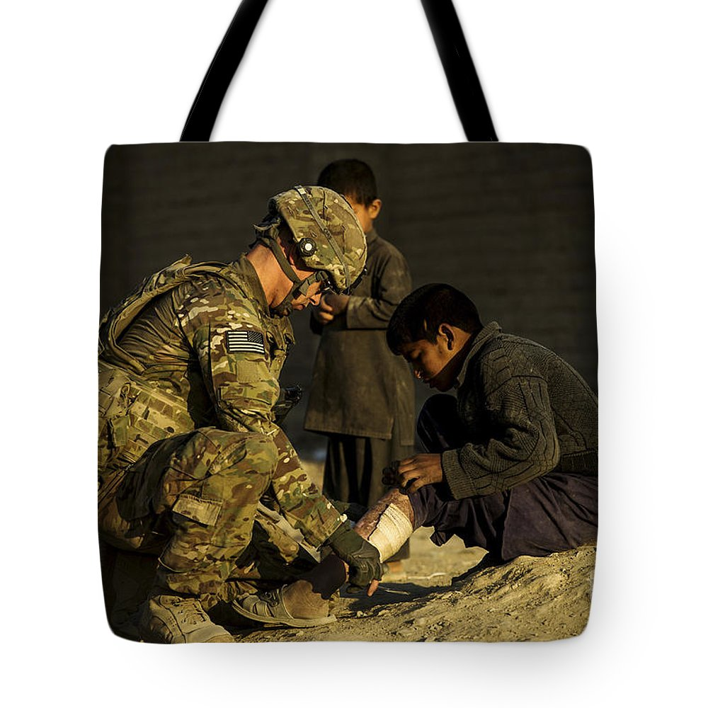 Air Force Tote Bag featuring the photograph Airman Provides Medical Aid To A Local by Stocktrek Images