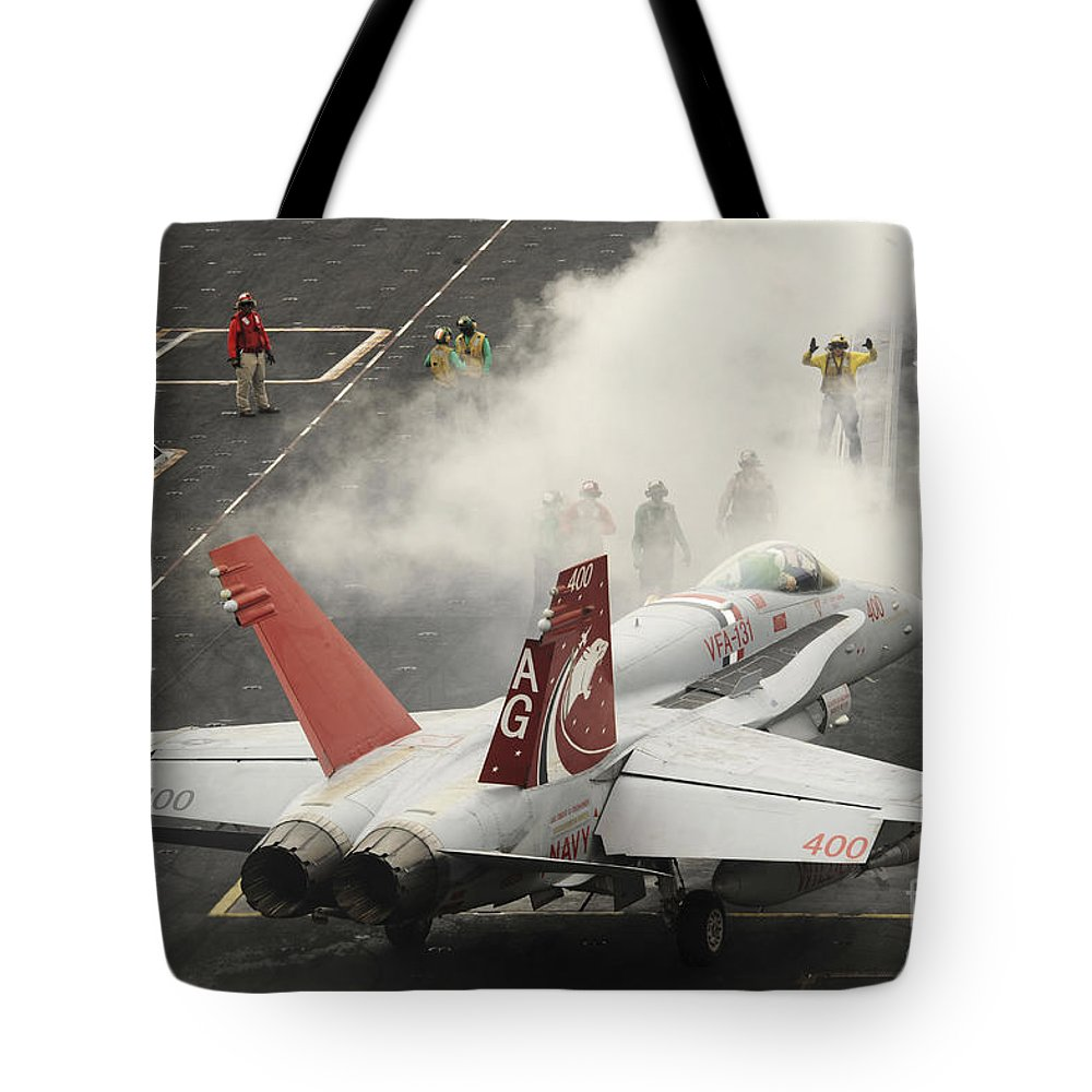 Military Tote Bag featuring the photograph An Fa-18c Hornet Prepares To Launch by Stocktrek Images