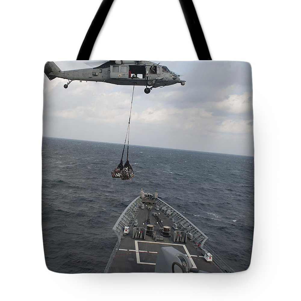 Military Tote Bag featuring the photograph An Mh-60s Sea Hawk Helicopter Delivers by Stocktrek Images