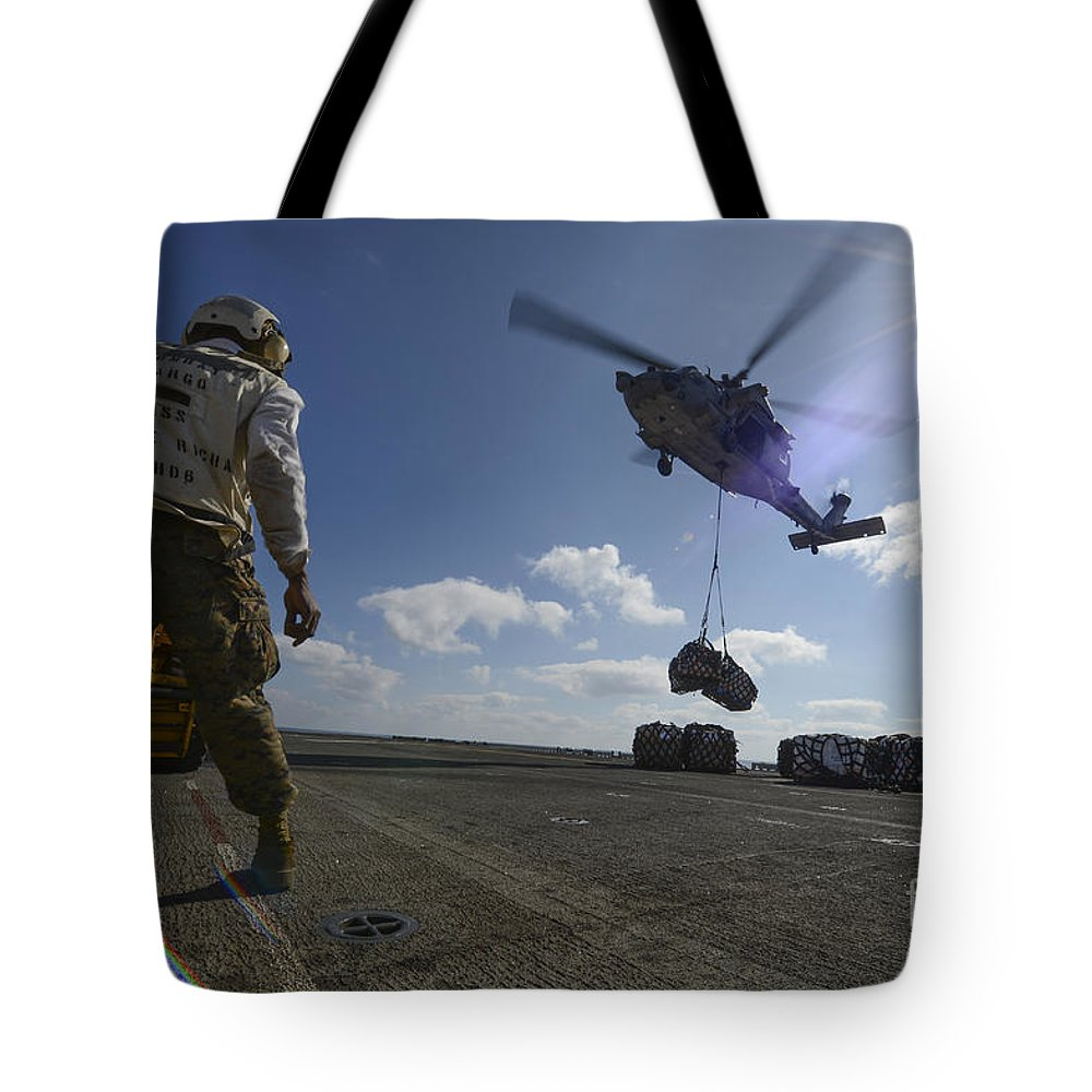 Military Tote Bag featuring the photograph An Mh-60s Sea Hawk Helicopter Lowers by Stocktrek Images