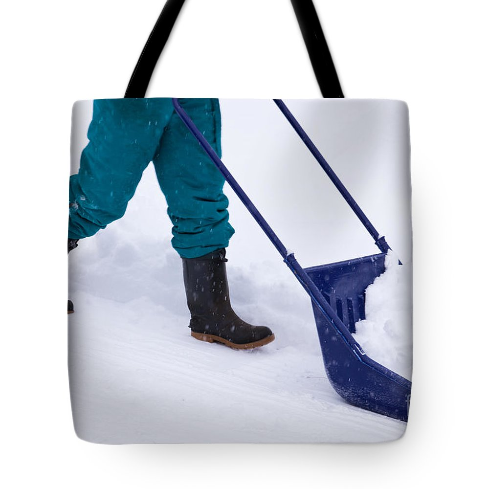 Black Tote Bag featuring the photograph Manual Snow Removal With Snow Scoop After Blizzard by Stephan Pietzko