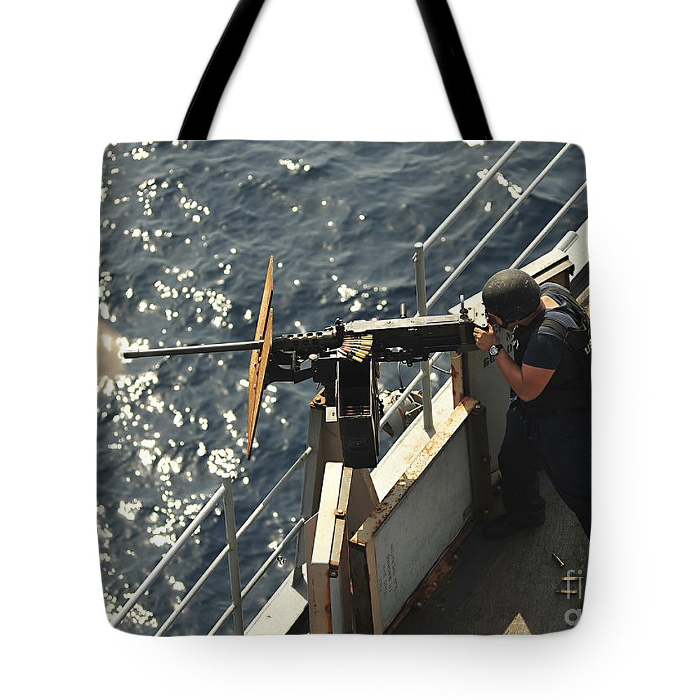 Us Navy Tote Bag featuring the photograph Seaman Fires A .50-caliber Machine Gun by Stocktrek Images