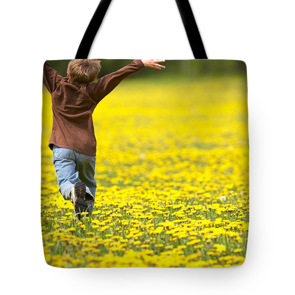 Light Tote Bag featuring the photograph Young Boy Running Through Field Of by Gemstone Images