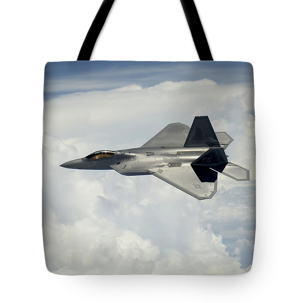 Us Air Force Tote Bag featuring the photograph A U.s. Air Force F-22 Raptor Aircraft by Stocktrek Images