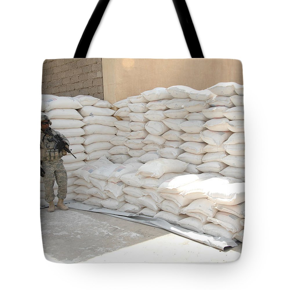 Military Tote Bag featuring the photograph A U.s. Soldier Provides Security by Stocktrek Images