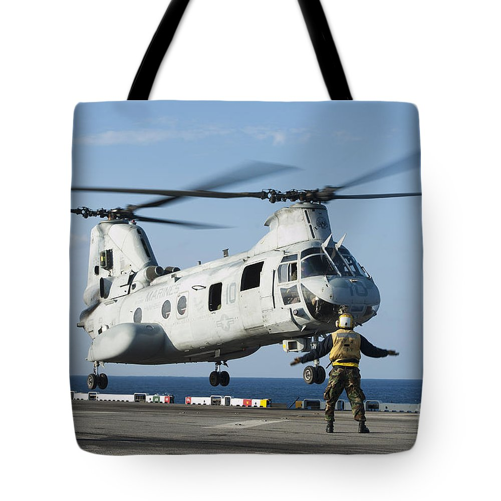 Military Tote Bag featuring the photograph An Aviation Boatswains Mate Directs by Stocktrek Images
