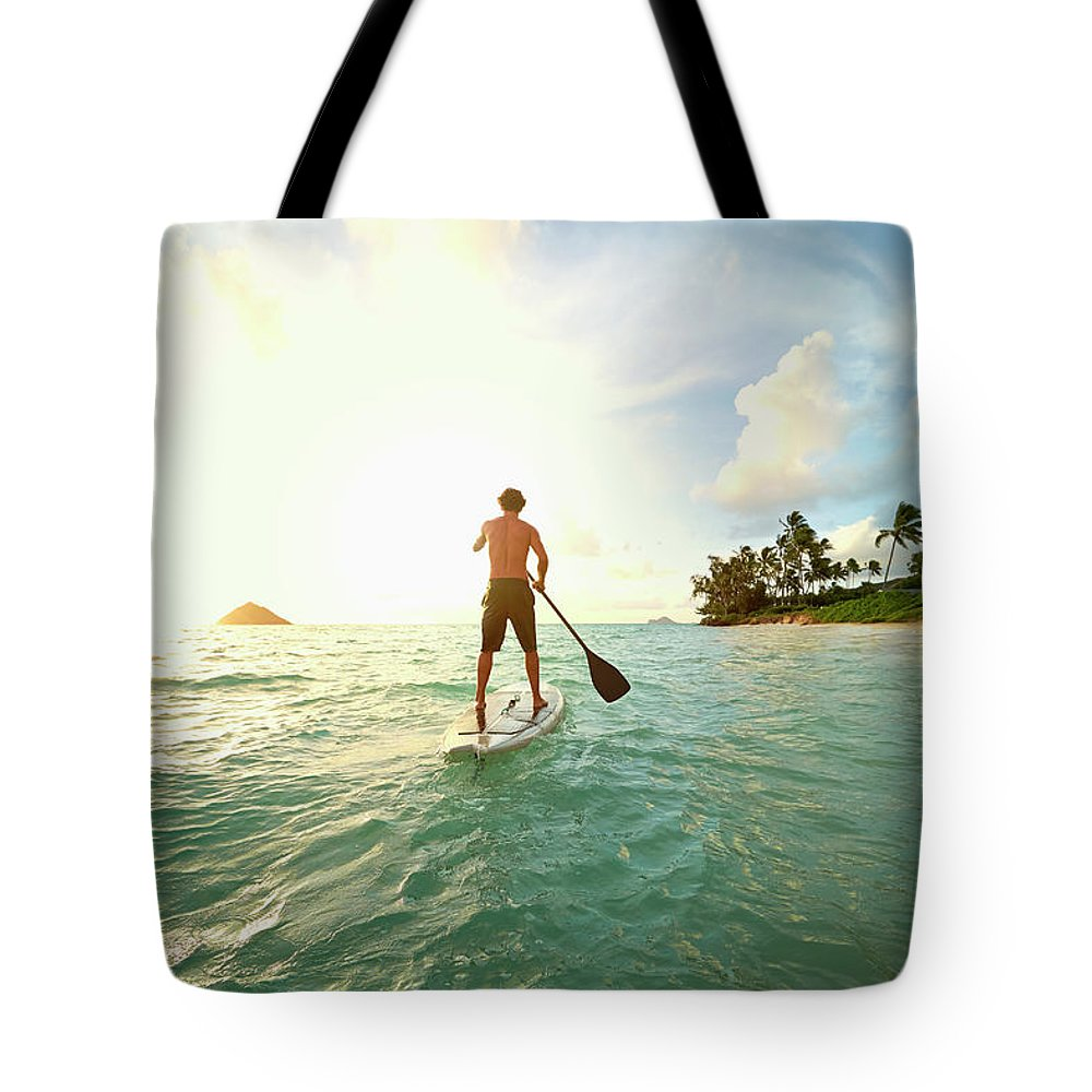 Tranquility Tote Bag featuring the photograph Caucasian Man On Paddle Board In Ocean by Colin Anderson Productions Pty Ltd