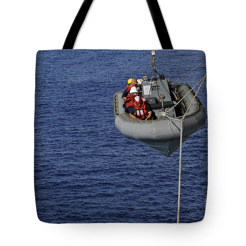 Military Tote Bag featuring the photograph Sailors Lower A Rigid-hull Inflatable by Stocktrek Images