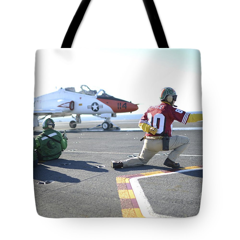 Military Tote Bag featuring the photograph Shooter Signals To The Pilot Of A T-45c by Stocktrek Images