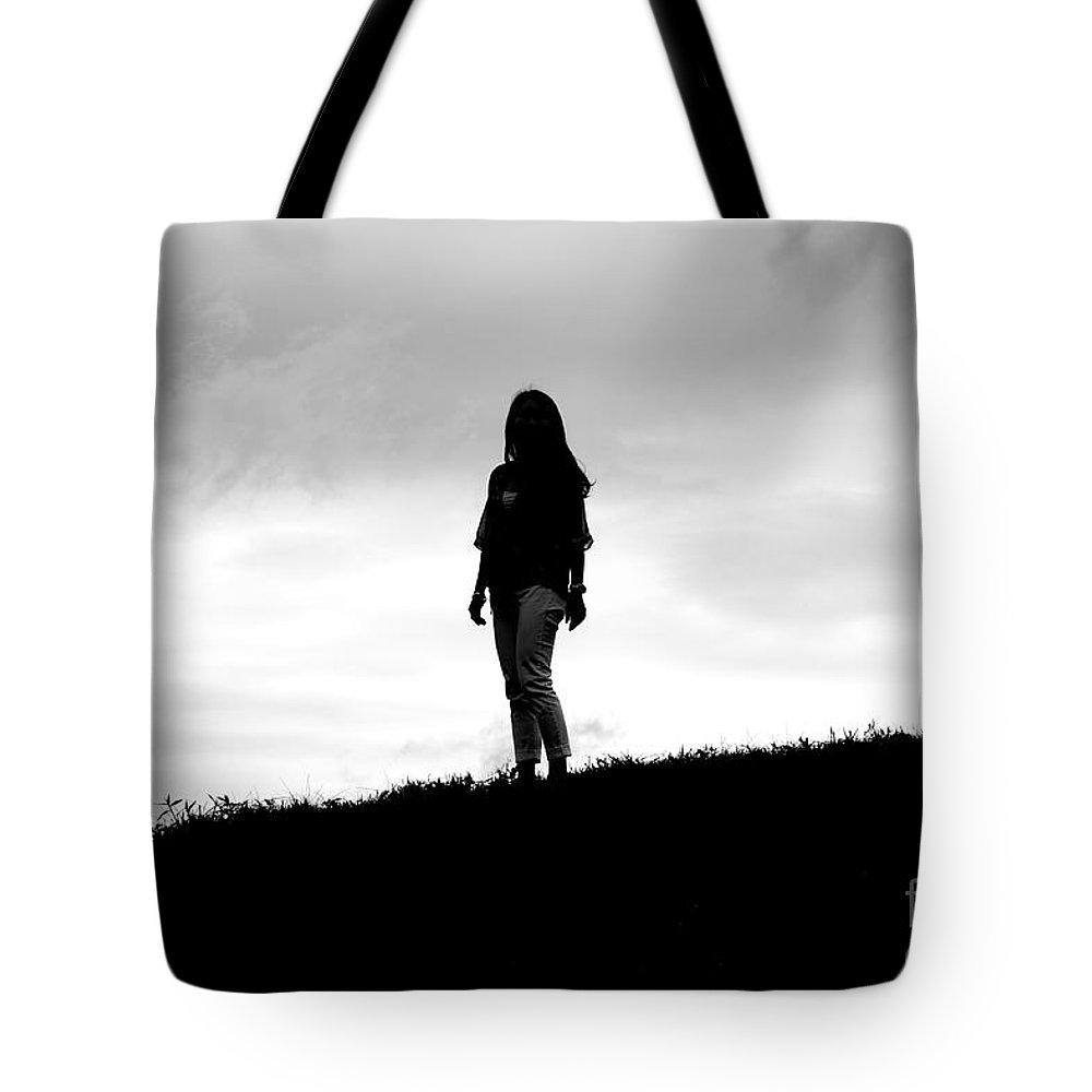 Nancy Lin Tote Bag featuring the photograph Silhouette Of Girl Against Overcast Sky by Jannis Werner