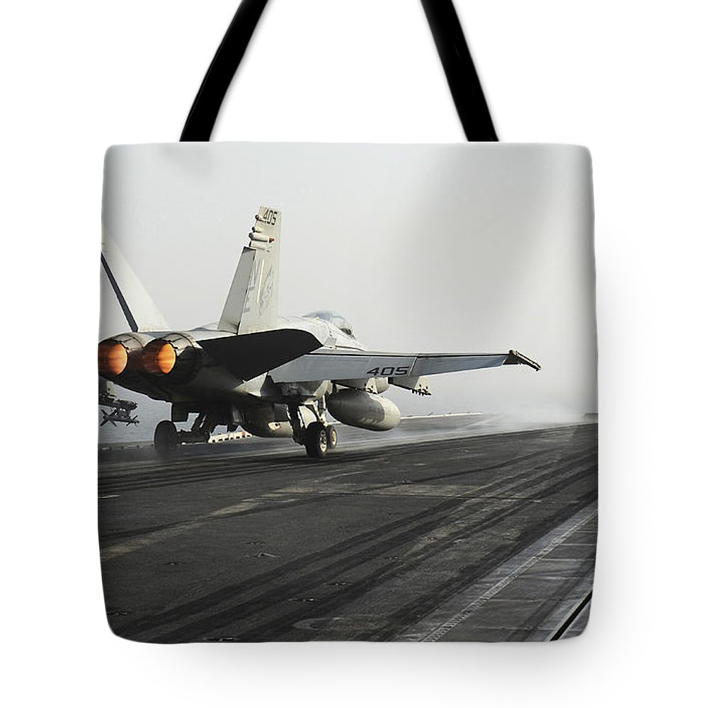 Uss Abraham Lincoln Tote Bag featuring the photograph An Fa-18c Hornet Launches by Stocktrek Images