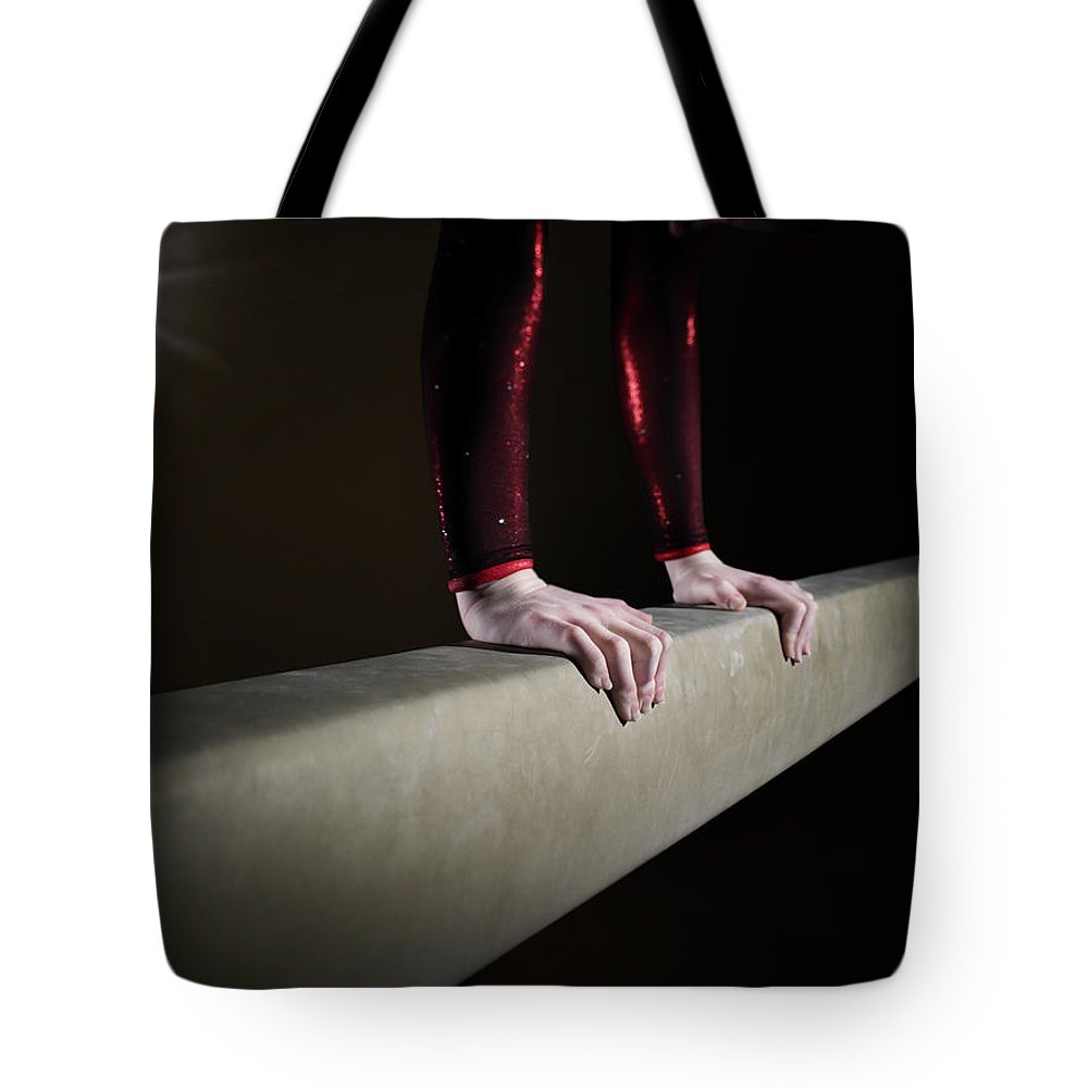 Human Arm Tote Bag featuring the photograph Female Gymnast On Balancing Beam by Mike Harrington