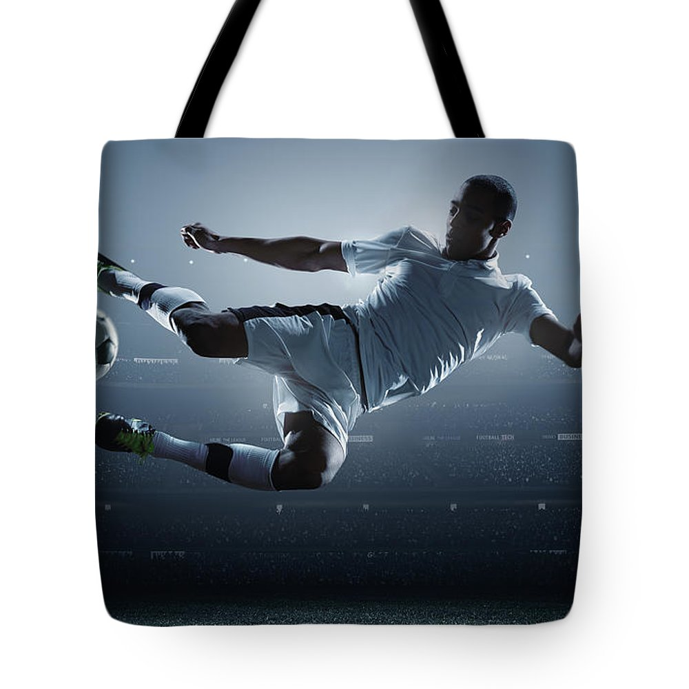 Goal Tote Bag featuring the photograph Soccer Player Kicking Ball In Stadium by Dmytro Aksonov