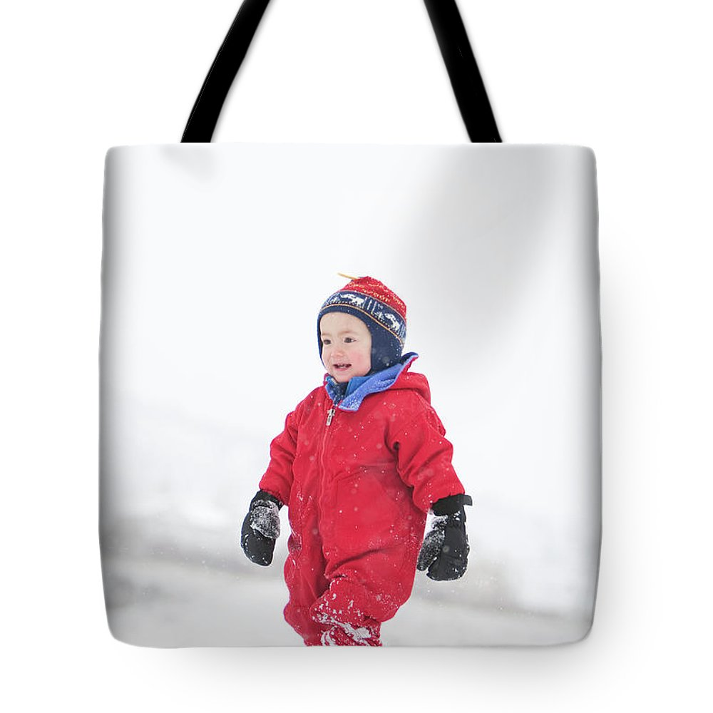 2-3 Years Tote Bag featuring the photograph A Two Year Old Boy Plays In A Snowy by Steve Glass