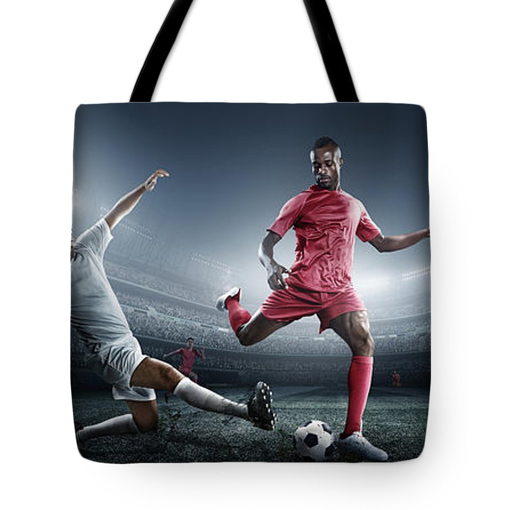 Soccer Uniform Tote Bag featuring the photograph Soccer Player Kicking Ball In Stadium by Dmytro Aksonov