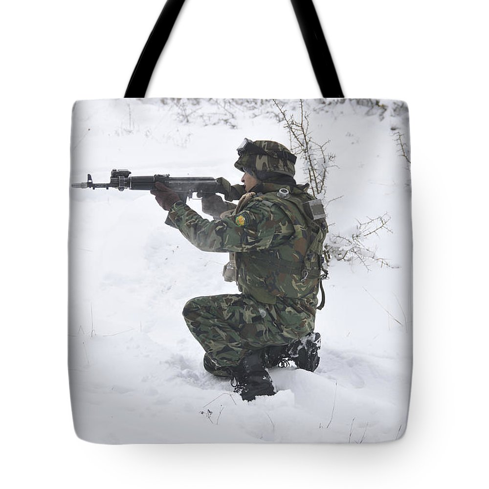 Military Tote Bag featuring the photograph A Bulgarian Soldier Aims Down The Sight by Stocktrek Images