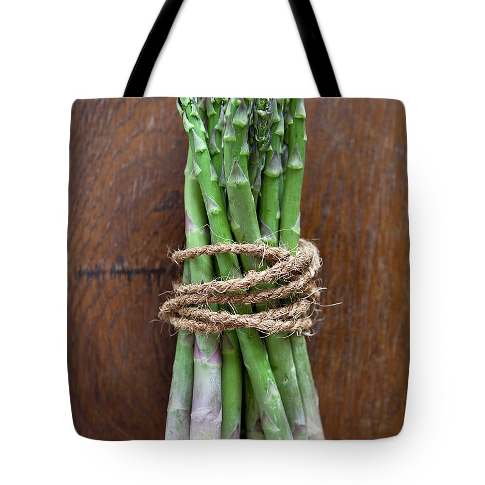 Kitchen Tote Bag featuring the photograph A Bundle Of Asparagus by Halfdark