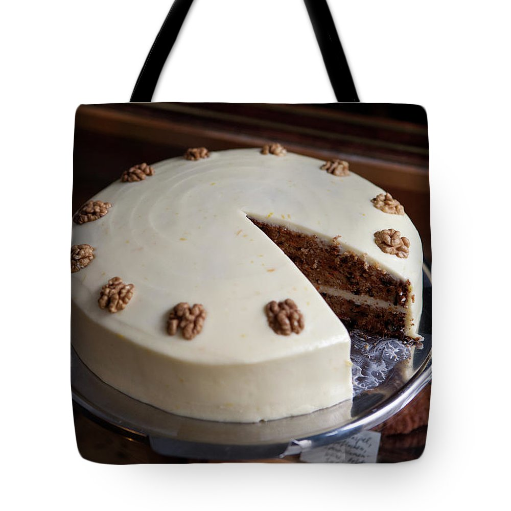 Unhealthy Eating Tote Bag featuring the photograph A Carrot Cake On A Display Cabinet In A by Halfdark