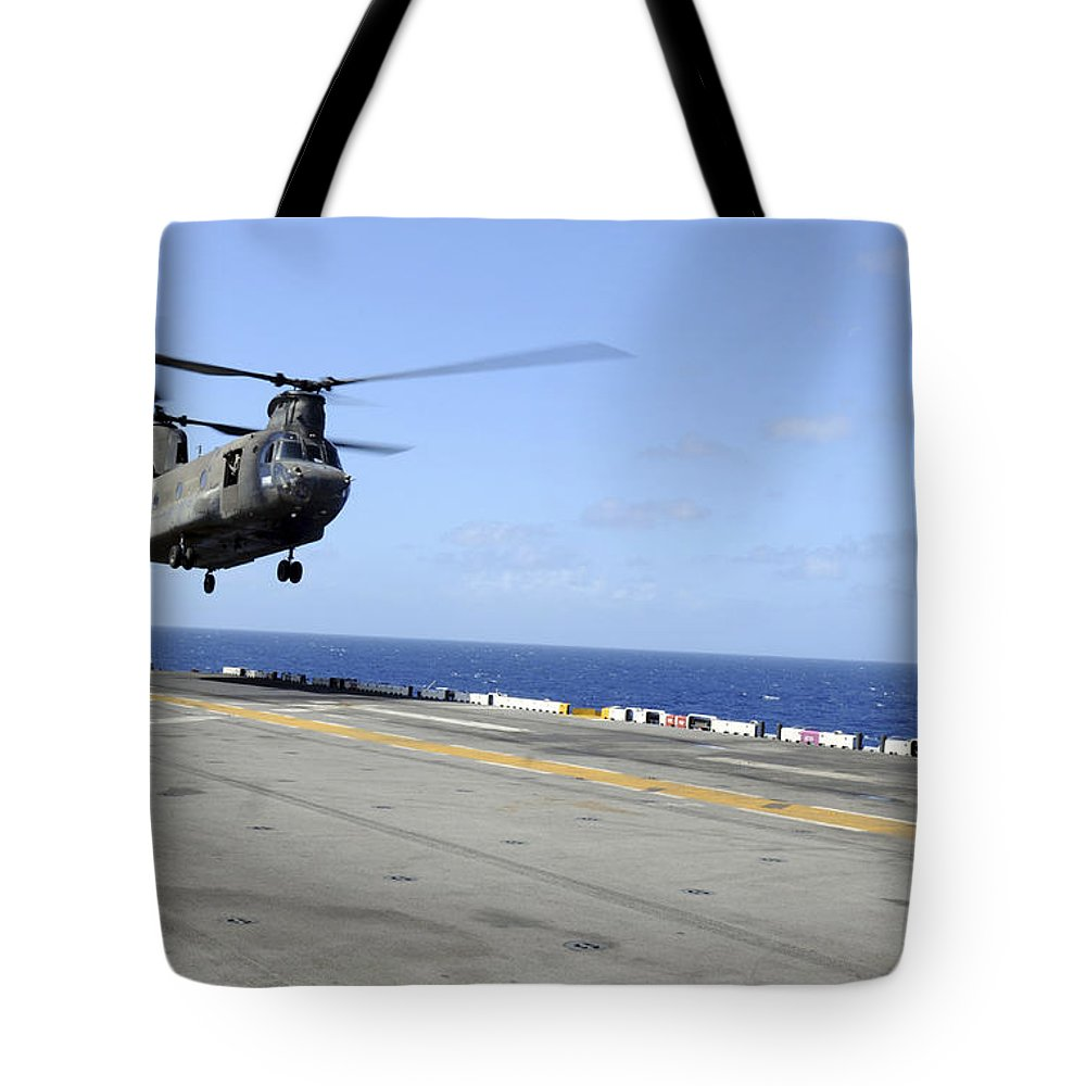 Uss Wasp Tote Bag featuring the photograph A Ch-47 Chinook Helicopter Landing by Stocktrek Images