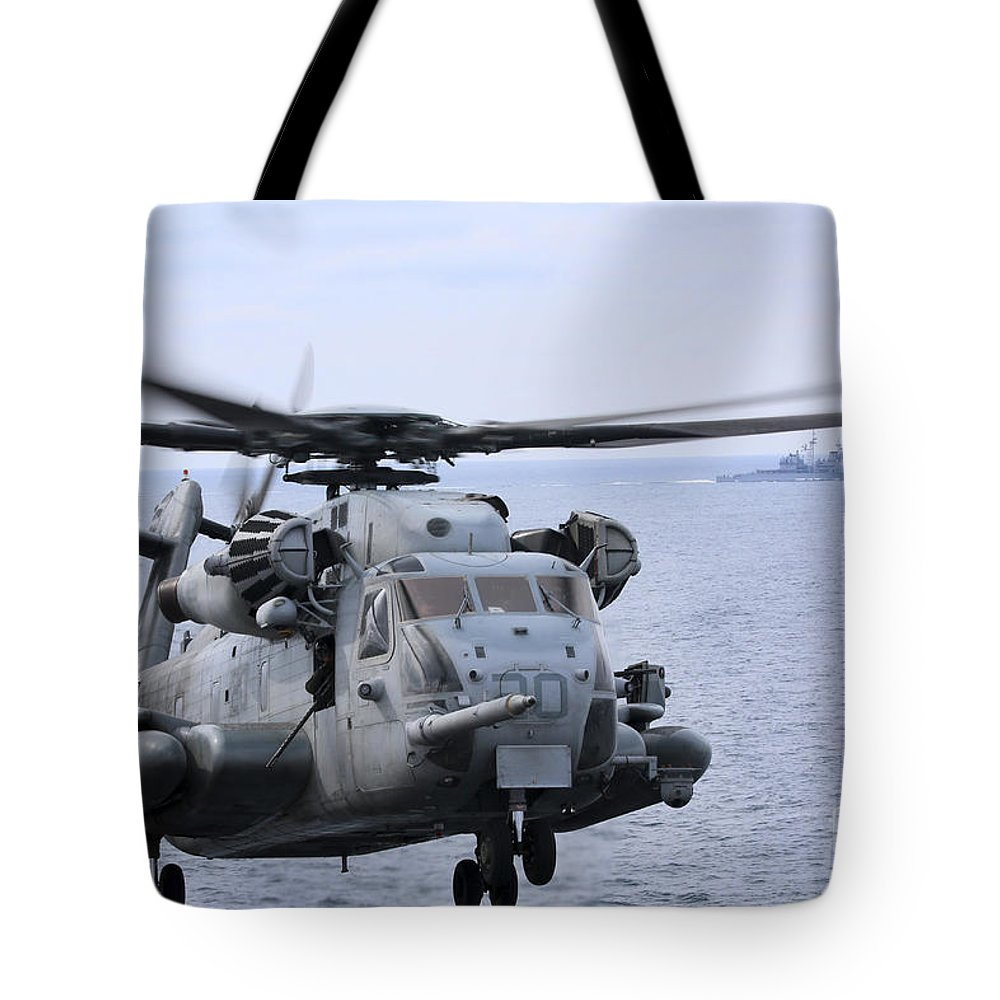 Military Tote Bag featuring the photograph A Ch-53e Super Stallion Conducts Flight by Stocktrek Images