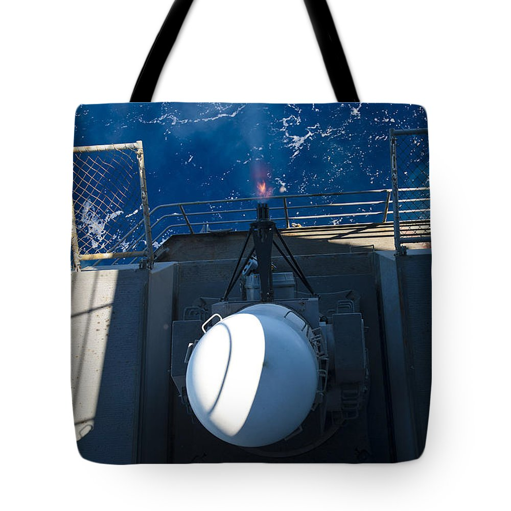 Military Tote Bag featuring the photograph A Closed-in Weapons System Fires by Stocktrek Images