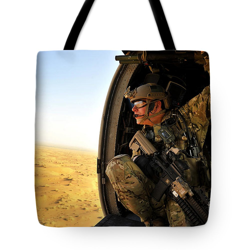 Hh-60 Pave Hawk Tote Bag featuring the photograph A Combat Rescue Officer Conducts by Stocktrek Images