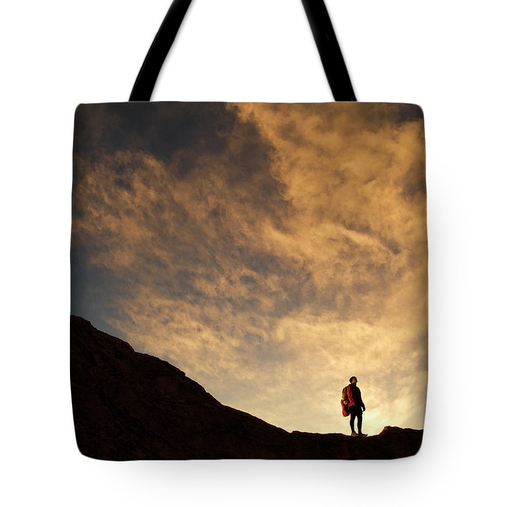 Backpack Tote Bag featuring the photograph A Hiker Standing On A Ridge At Sun Rise by Keith Ladzinski