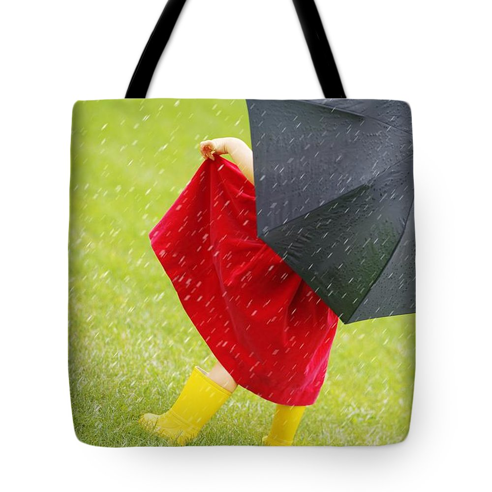 Outdoors Tote Bag featuring the photograph A Little Girl Walking In The Rain While by Leah Hammond