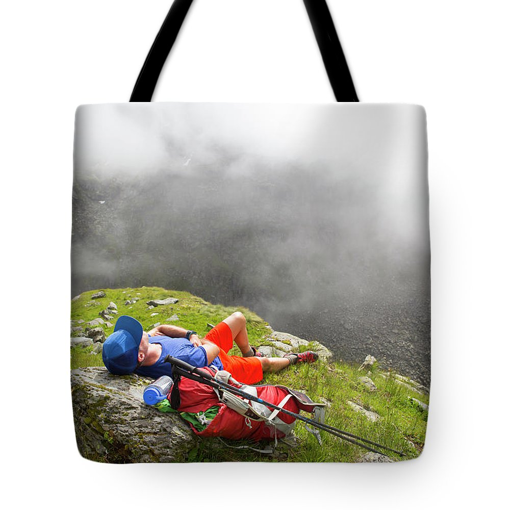 Valais Tote Bag featuring the photograph A Male Hiker Is Resting In A Grassy by Menno Boermans