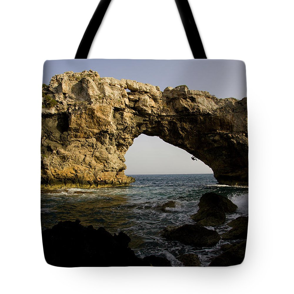 Action Tote Bag featuring the photograph A Man Rock Climbing Deep Water Soloing by Corey Rich