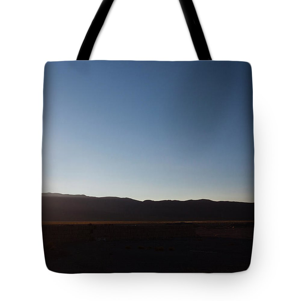 Sunset Tote Bag featuring the photograph A Man Stands On A Wall In The Salar De by Michael Hanson