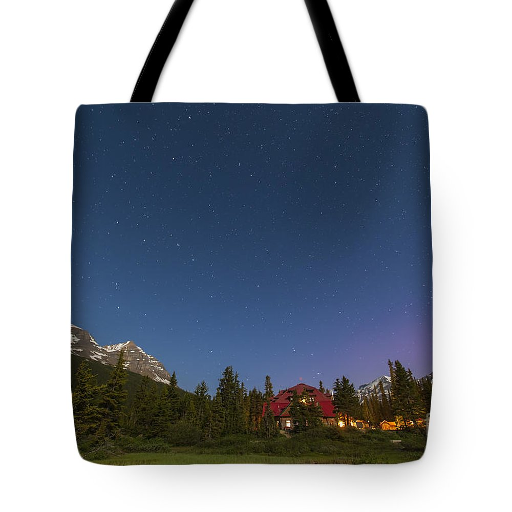 Aurora Borealis Tote Bag featuring the photograph A Moonlit Nightscape Taken In Banff by Alan Dyer