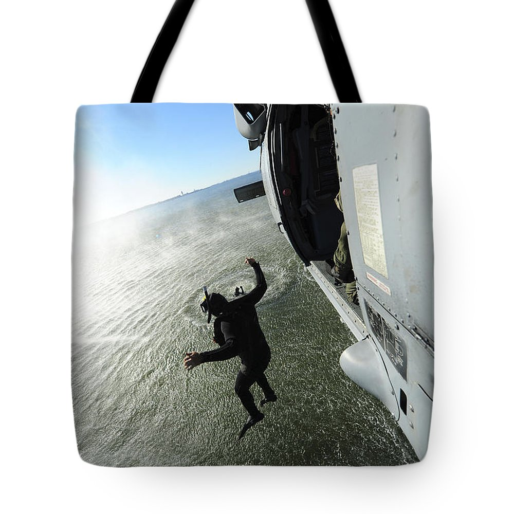 Military Tote Bag featuring the photograph A Naval Air Crewman Jumps From An by Stocktrek Images