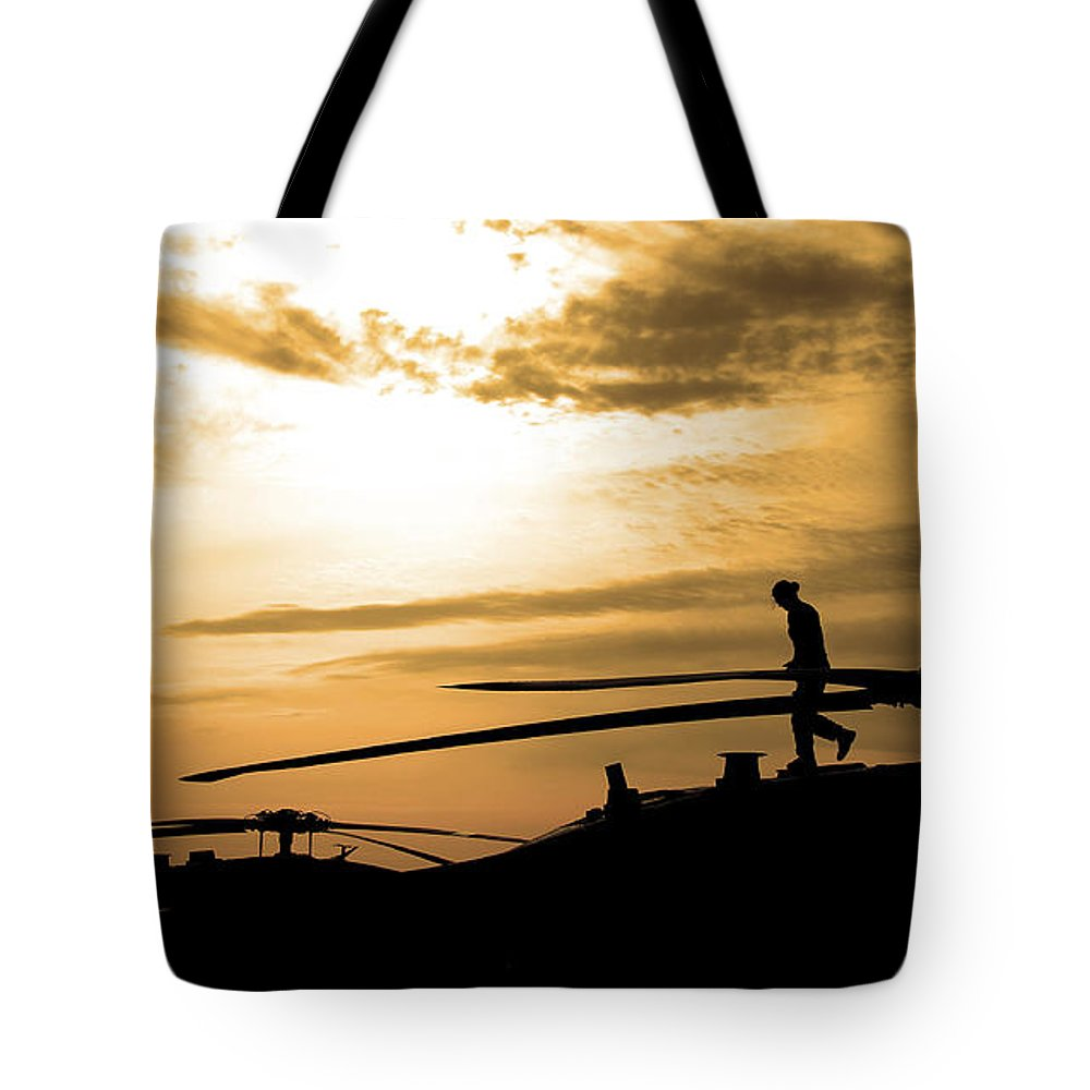 Sunrise Tote Bag featuring the photograph A Pilot Conducts A Pre-flight by Stocktrek Images