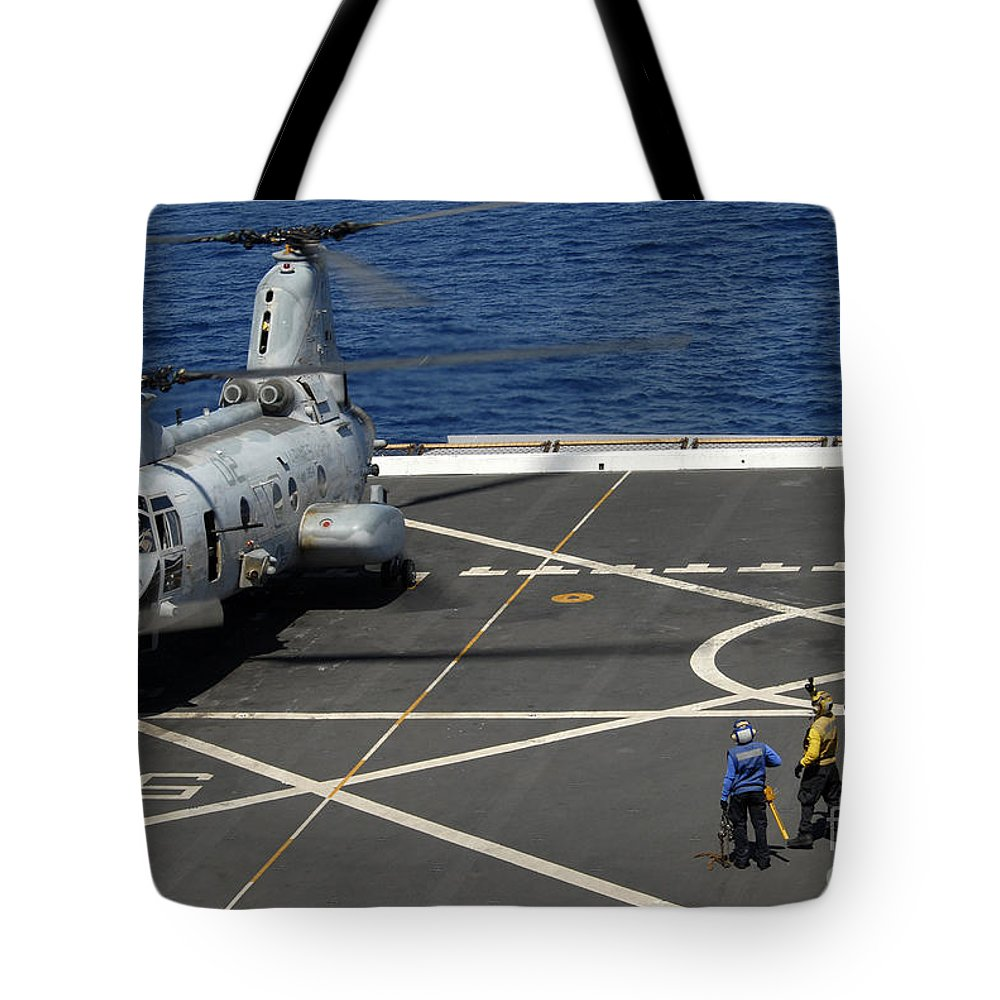 Military Tote Bag featuring the photograph A Plane Captain Signals To A Ch-46e Sea by Stocktrek Images