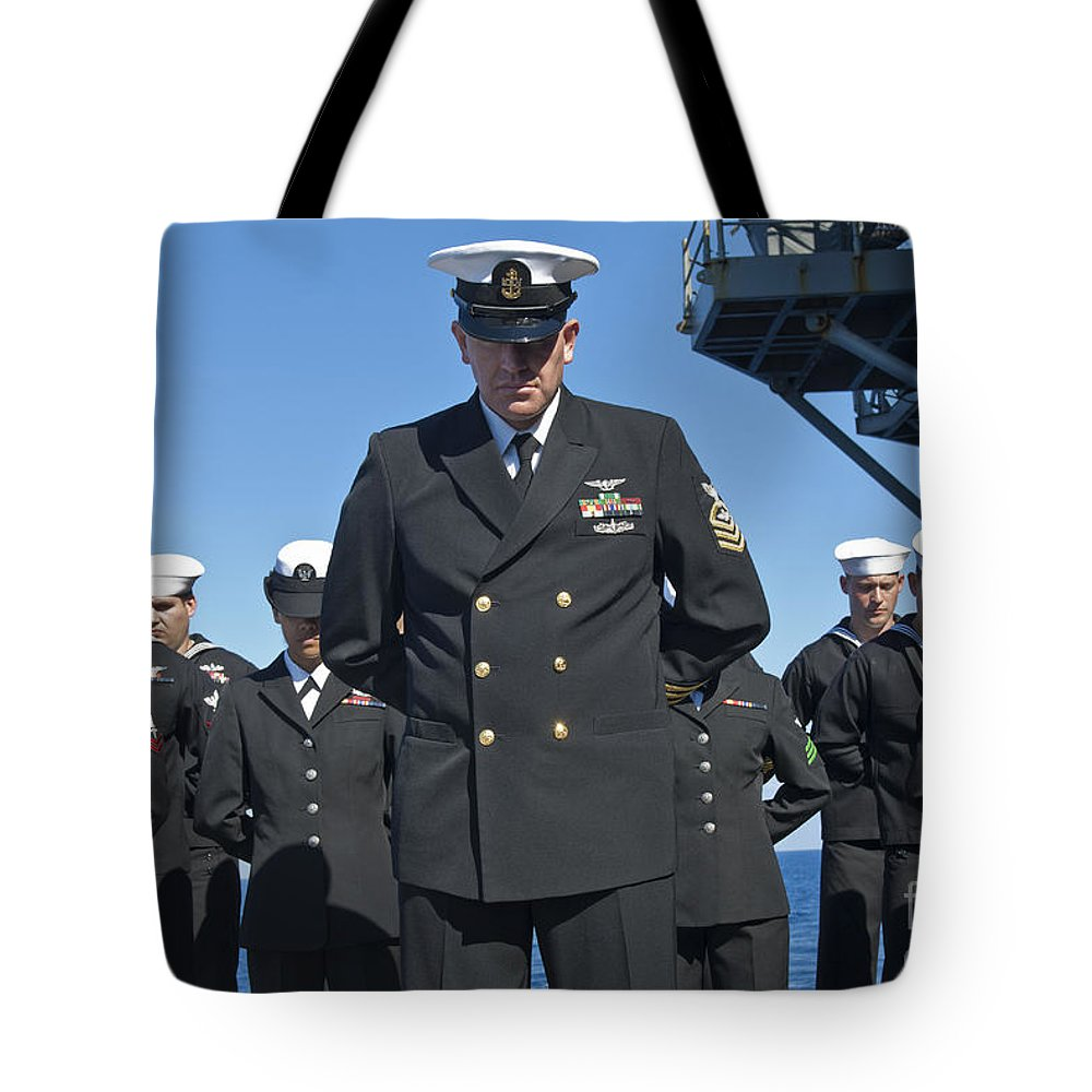 Military Tote Bag featuring the photograph A Prayer Is Delivered During A Burial by Stocktrek Images