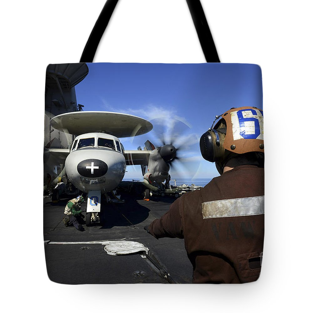 Military Tote Bag featuring the photograph A Sailor Signals To Pilots Of An E-2c by Stocktrek Images