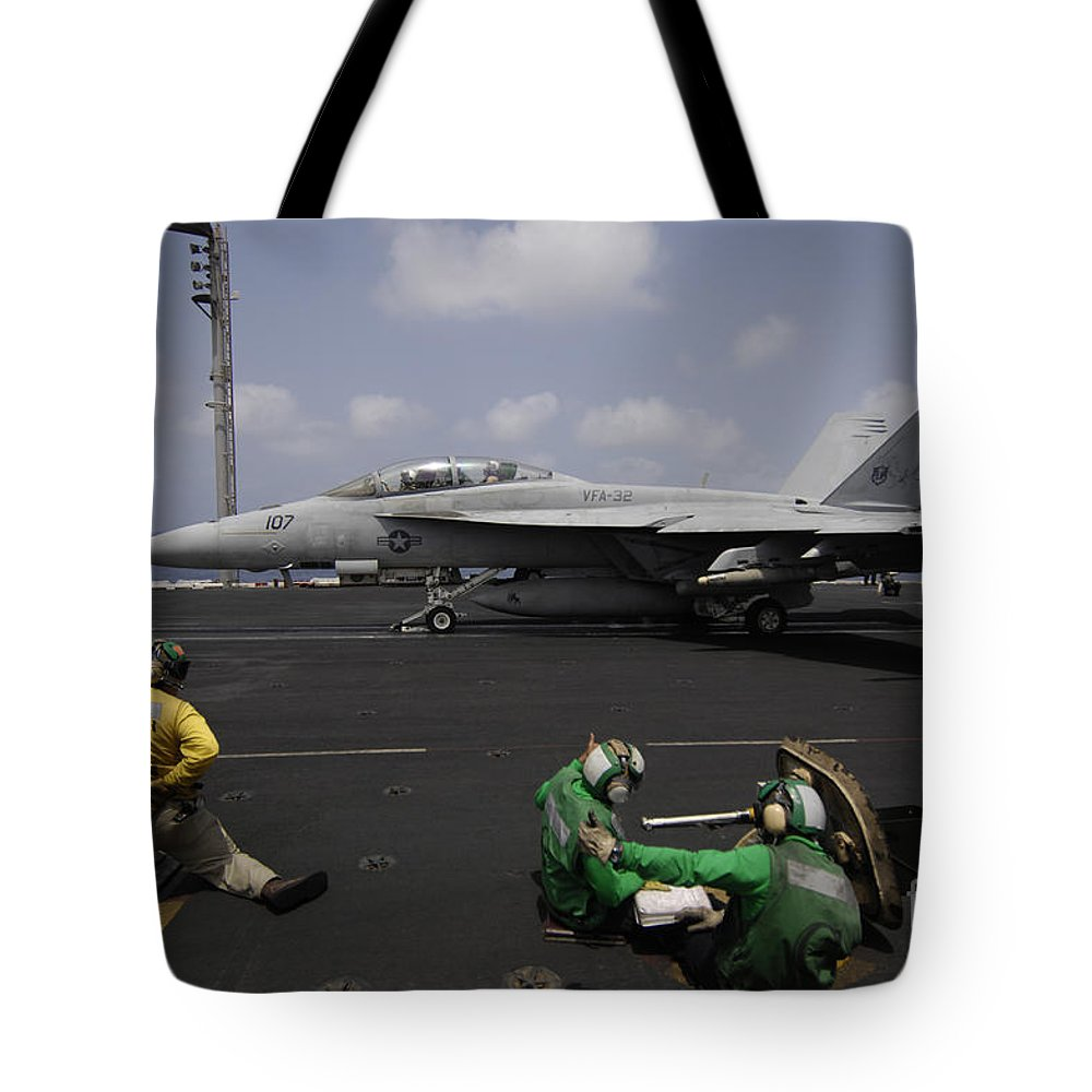 Uss Harry S Truman Tote Bag featuring the photograph A Shooter Signals For The Launching by Stocktrek Images
