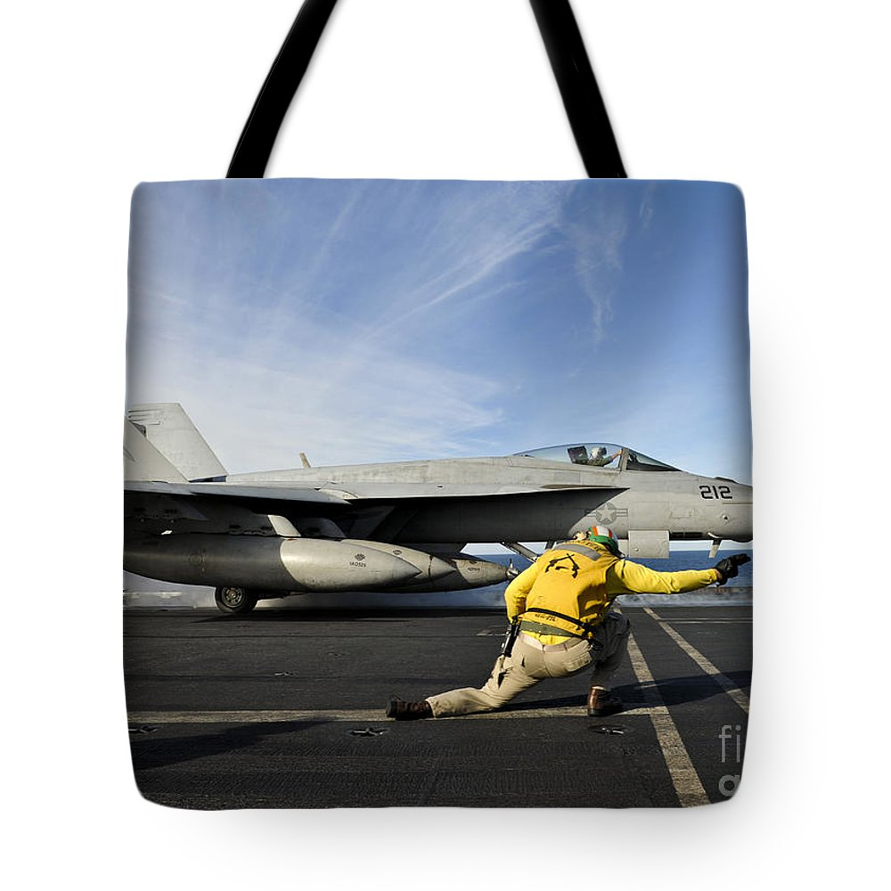 Military Tote Bag featuring the photograph A Shooter Signals To Launch An Fa-18e by Stocktrek Images