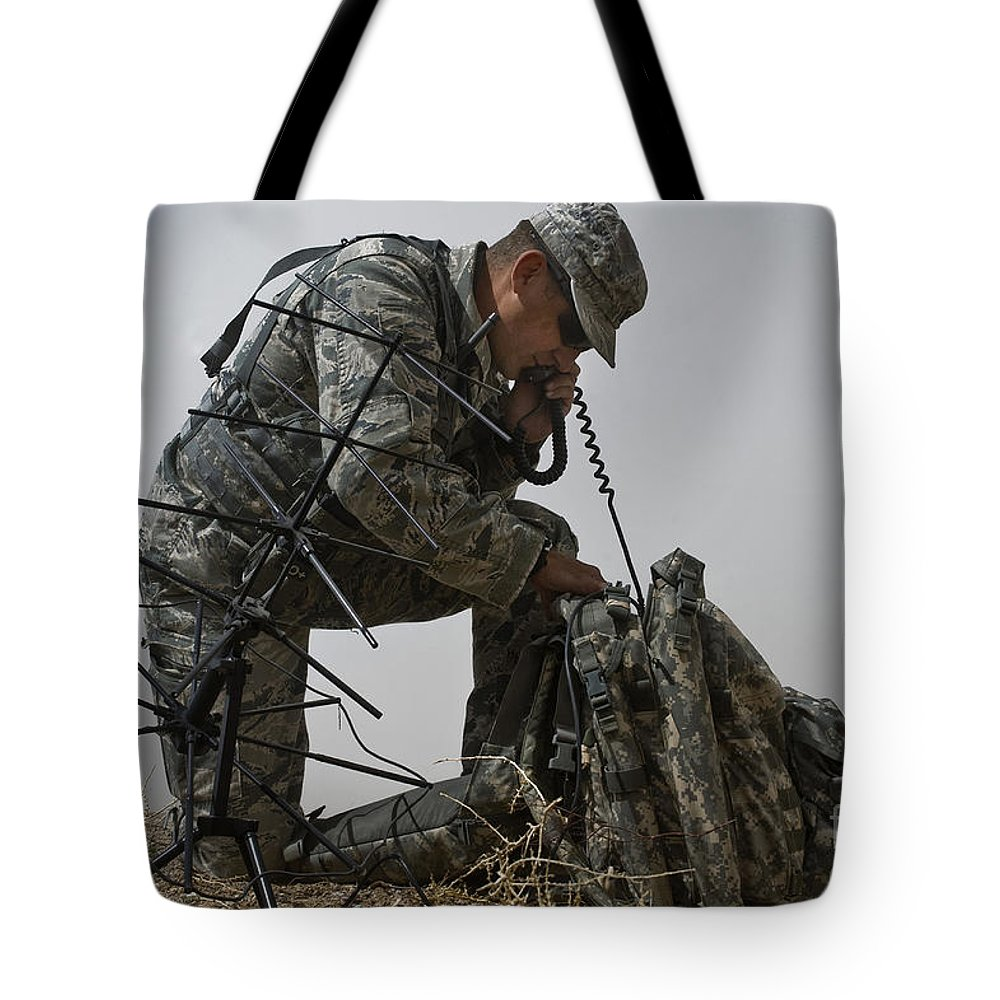 Army Tote Bag featuring the photograph A Soldier Communicates Using A by Stocktrek Images