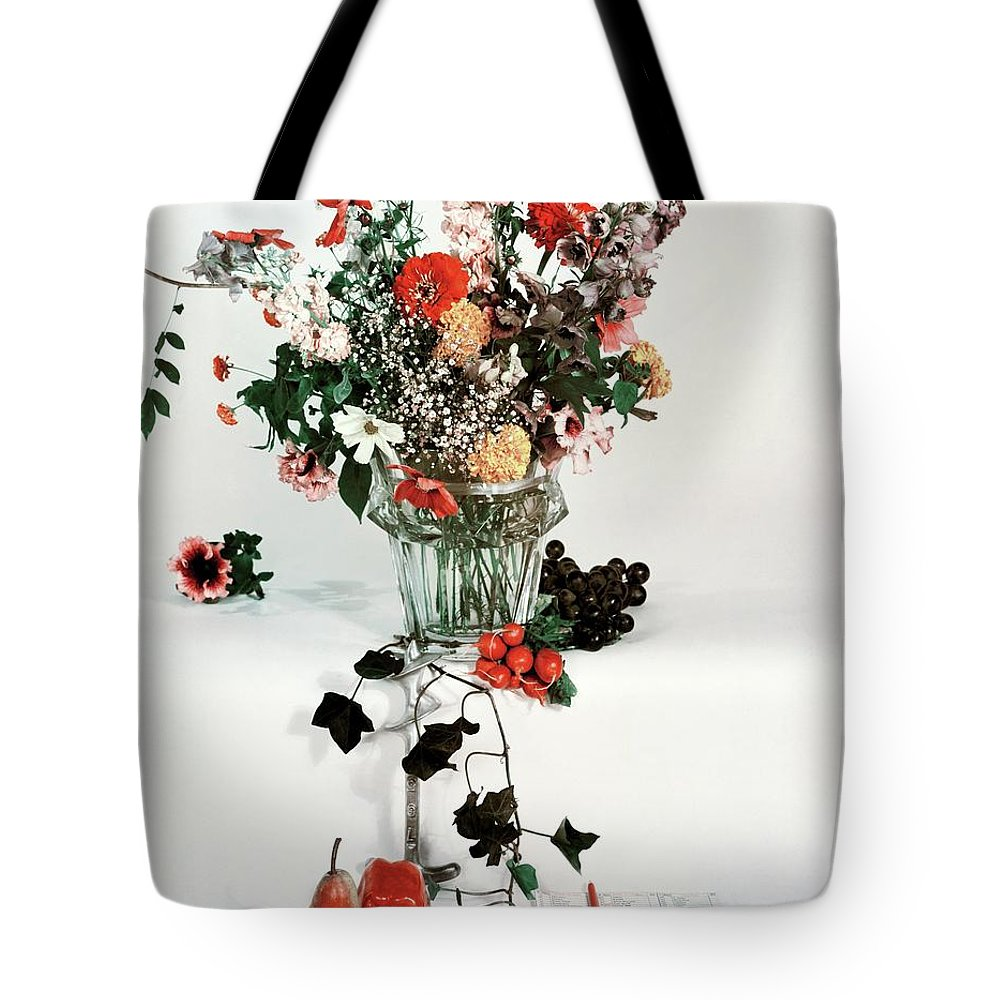 Nobody Tote Bag featuring the photograph A Studio Shot Of A Vase Of Flowers And A Garden by Herbert Matter